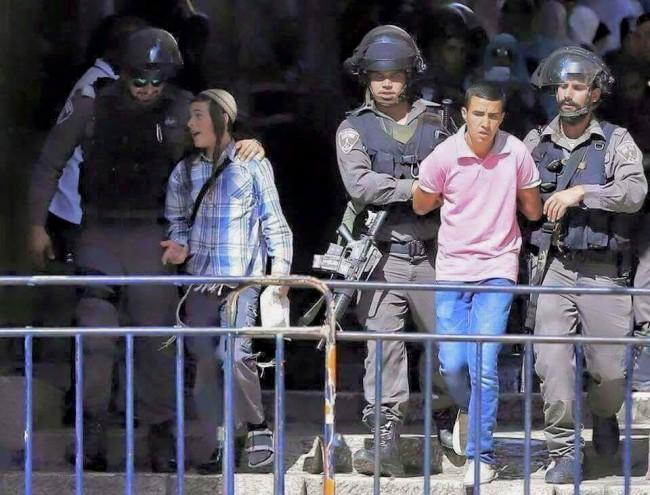 Privođenje na cionistički način: Palestinskom dječaku lisice na rukama, a jevreju zagrljaj