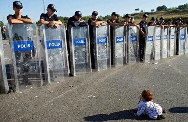 Sirijska beba puzi pred grčkim graničarima
